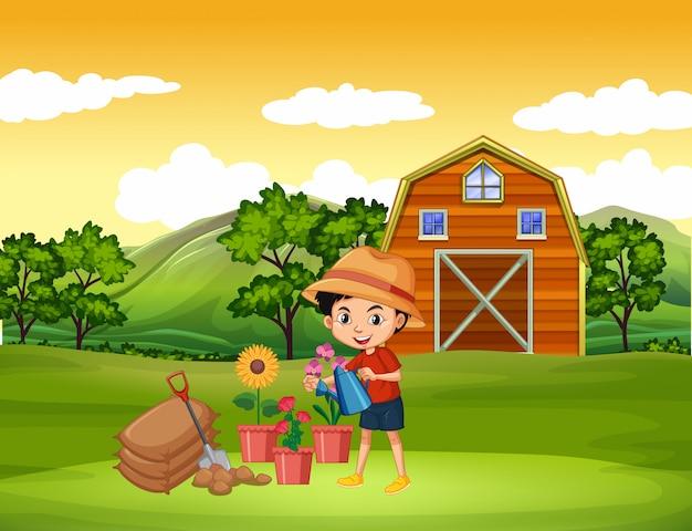 Rolna scena z chłopiec nawadnia kwiaty na gospodarstwie rolnym