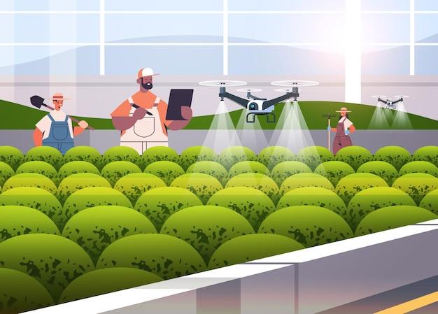 Rolnicy rasy mieszanej kontrolujący drony rolnicze opryskiwacze quady helikoptery lecące do rozpylania nawozów chemicznych w szklarniach innowacyjna technologia inteligentnego rolnictwa