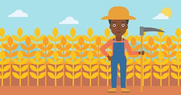 Rolnik na polu z kosą