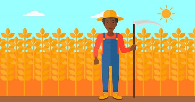 Rolnik na polu z kosą.