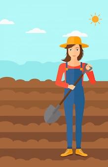 Rolnik na polu z łopatą.
