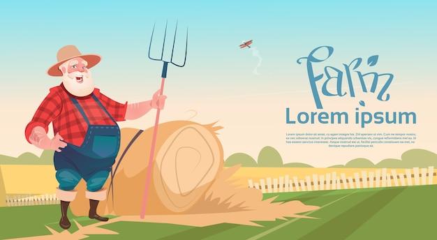 Rolnik pracuje na gospodarstwie przechowywania pitchfork zbiorów siana