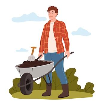 Rolnik w kraciastej koszuli spycha taczkę z ziemi