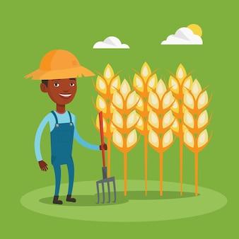 Rolnik z widłami na polu pszenicy.