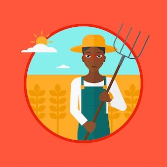 Rolnik z widłami w polu pszenicy.
