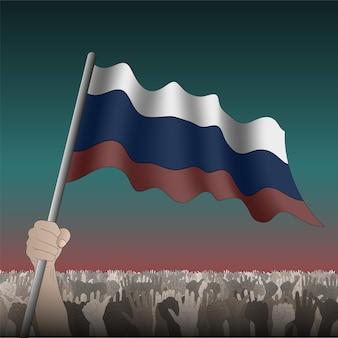 Rosyjska flaga macha w ręku wśród tłumu.