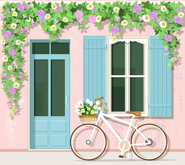 Rower z kwiatami w pobliżu domu w stylu prowansalskim