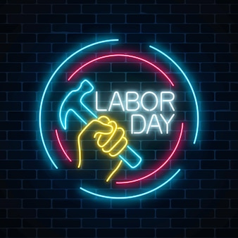 Rozjarzony neonowy święto pracy podpisuje wewnątrz okrąg ramy na ciemnym ściana z cegieł tle. światowy dzień pracy symbol z młotem w ręku