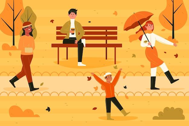 Różni ludzie chodzą po parku jesienią