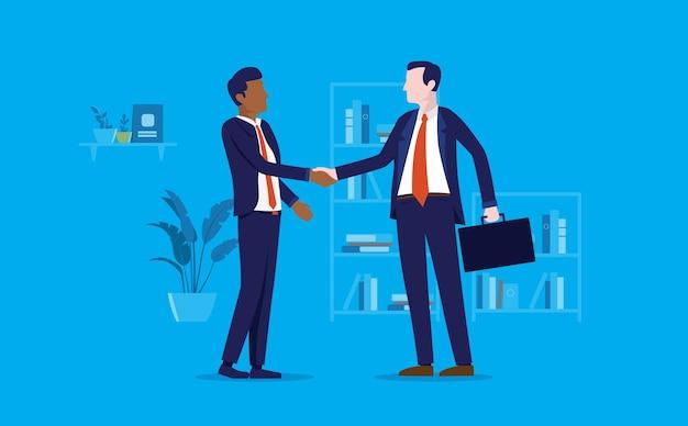 Różnorodny uścisk dłoni między dwoma mężczyznami w biurze dokonującymi transakcji biznesowej