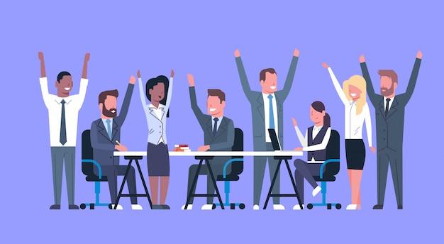 Rozochocona biznes drużyna siedzi wpólnie przy biurko szczęśliwą grupą pomyślni biznesmeni z nastroszony