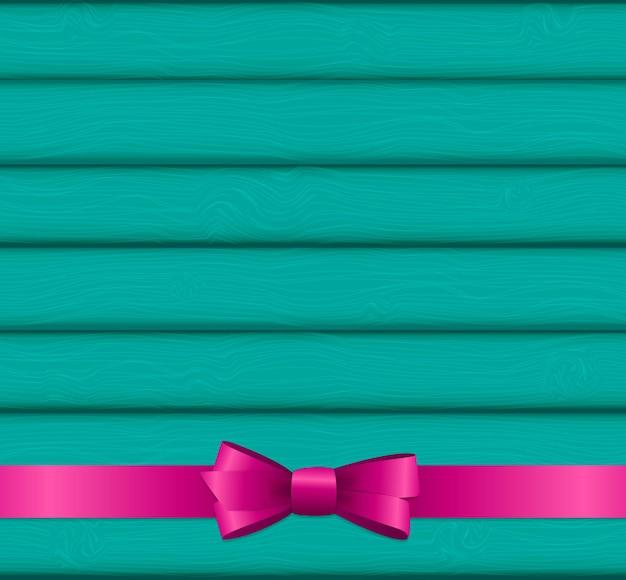 Różowa wstążka i kokarda na drewnianym tle na urodziny chrystusa