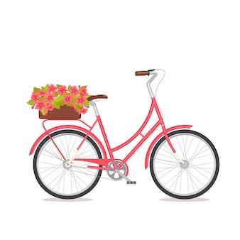 Różowy retro bicykl z bukietem w kwiecistym pudełku na bagażniku.