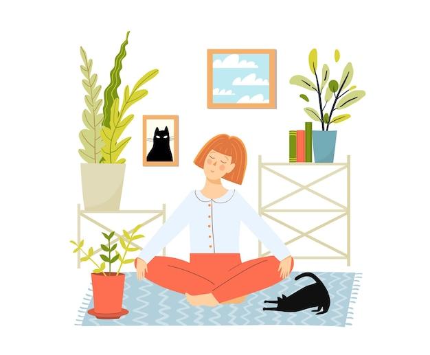 Rudowłosa młoda kobieta robi joga i medytację w domu