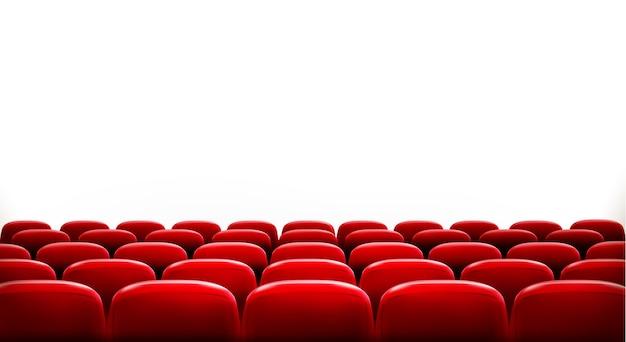 Rzędy czerwonych miejsc kinowych lub teatralnych przed białym pustym ekranem z miejscem na przykładowy tekst.