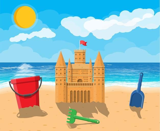 Rzeźba z zamku z piasku. plastikowe wiadro z grabiami, łopatą. twierdza z wieżami.
