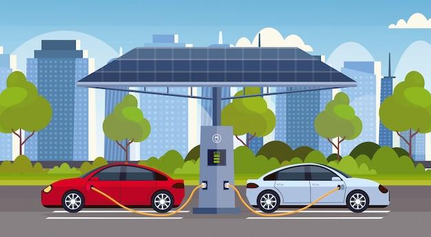 Samochody elektryczne ładujące na stacji ładowania elektrycznego z paneli słonecznych odnawialny ekologiczny transport środowiska opieki koncepcja nowoczesny pejzaż miejski tło poziome