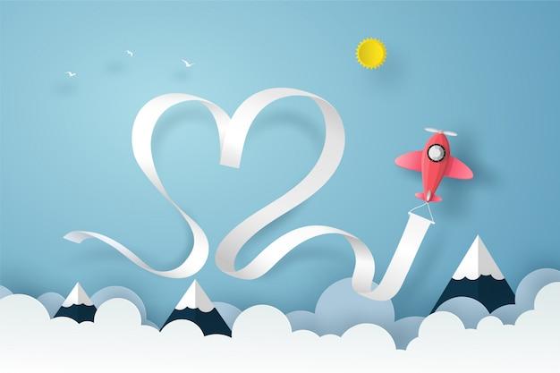 Samolot latający na niebieskim niebie nad chmurami i górą z faborkiem dymu i serca