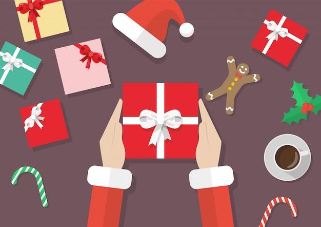 Santa ręki trzyma prezenta pudełko z boże narodzenie elementami