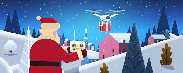 Santa trzymać kontroler usługi dostarczania dronów w nocy zimowych domów wsi