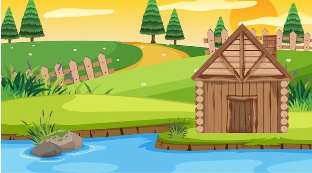 Scena z drewnianą chałupą w polu przy zmierzchem
