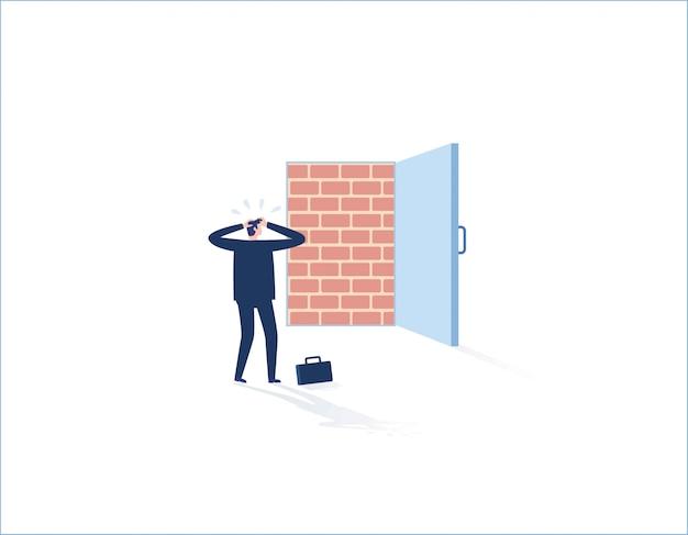 Ściana z cegieł blokuje drzwi do biura, biznesmen stoi posępnie. przeciwności losu, uwięziona przeszkoda, bez wyjścia.
