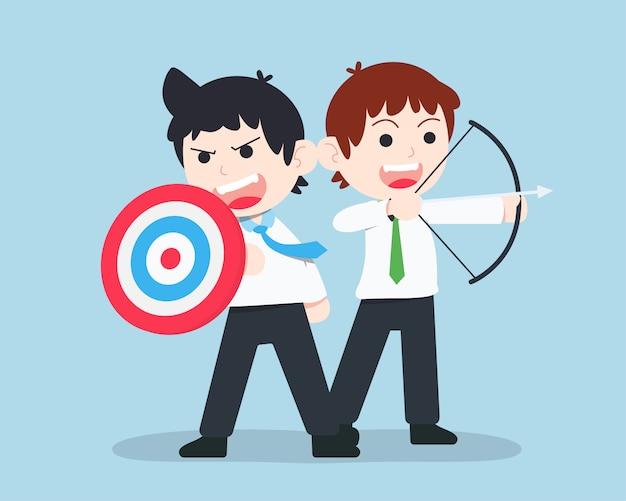 Sd business man stoi i trzyma tarczę w formie celu, a koledzy trzymają łuk