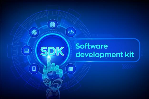 Sdk. koncepcja zestawu do tworzenia oprogramowania na ekranie wirtualnym. robotyczna ręka dotykająca interfejs cyfrowy.