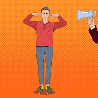 Sfrustrowany mężczyzna w stylu pop-artu zakrył uszy palcami z megafonu. pojęcie ignorancji.