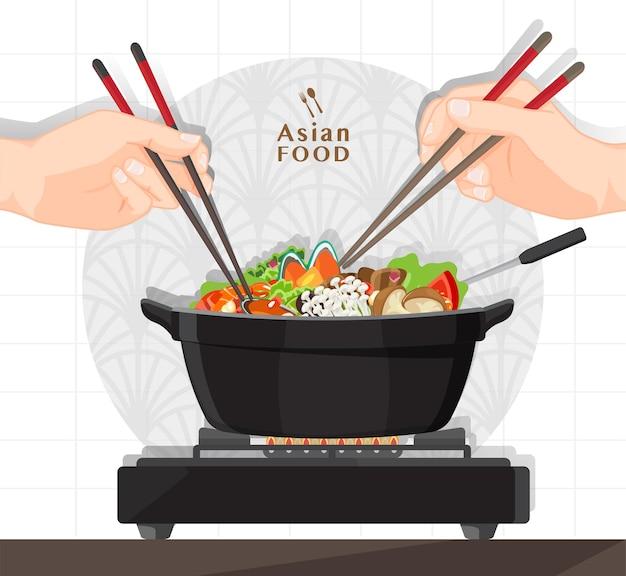 Shabu shabu i sukiyaki w gorącym garnku w restauracji, dłoń trzymająca pałeczki jedząca shabu shabu