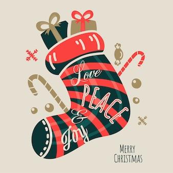 Skarpeta świętego mikołaja wypełniona prezentami, cukierkami, płatkami śniegu i tekstem love peace & joy na beżowym tle na wesołych świąt.