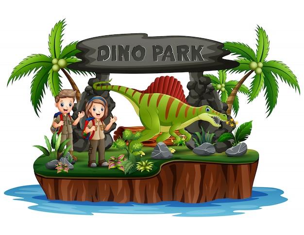 Skaut chłopiec i dziewczynka z dinozaurami w parku dino
