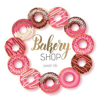 Sklep sweet bakery rama z przeszklonymi różowymi i czekoladowymi pączkami i ręcznie robionym napisem
