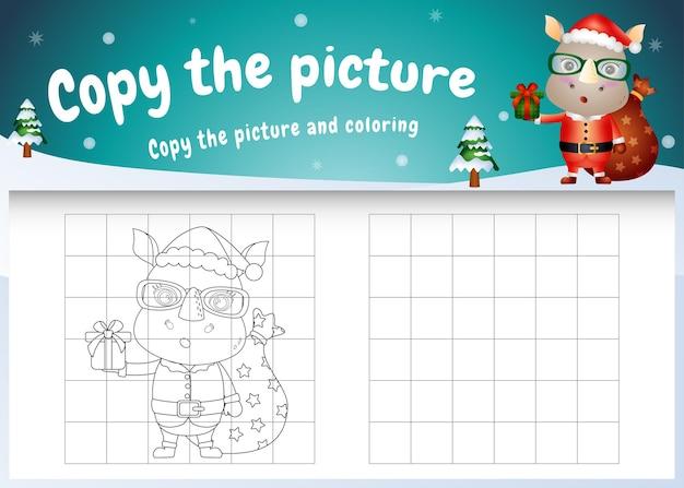 Skopiuj obrazek gry dla dzieci i stronę do kolorowania z uroczym nosorożcem za pomocą kostiumu świętego mikołaja