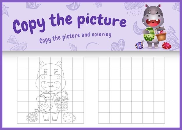 Skopiuj obrazkową grę dla dzieci i koloruj wielkanocną stronę o tematyce z uroczym hipopotamem trzymającym jajko w kształcie wiadra i pisankę