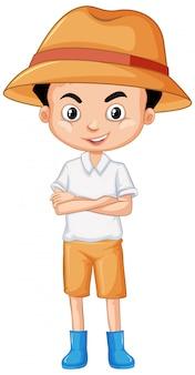 Śliczna chłopiec jest ubranym buty i kapelusz na bielu