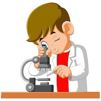 Śliczna chłopiec patrzeje przez mikroskopu