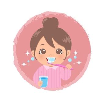 Śliczna dziewczyna szczotkuje zęby szczoteczką, trzymając szklankę wody
