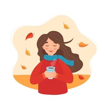 Śliczna dziewczyna trzyma filiżankę z jesienią i liśćmi.