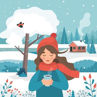 Śliczna dziewczyna trzyma filiżankę z zima śniegiem i krajobrazem w zimie.