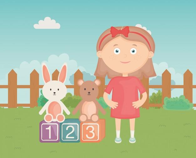 Śliczna dziewczyna z bloku królikiem i niedźwiedzia parkiem, dzieci zabawki
