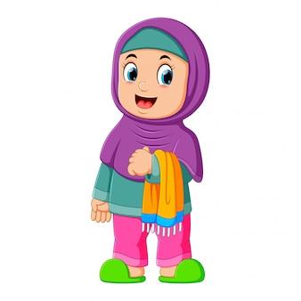 Śliczna dziewczyna z fioletowym welonem stoi i trzyma swój dywanik modlitewny