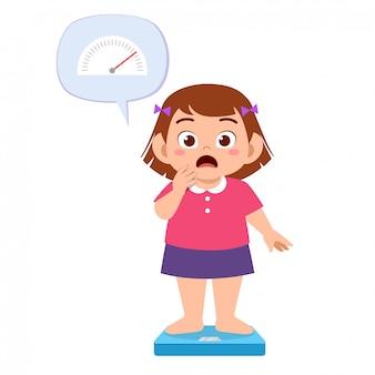 Śliczna gruba dzieciak dziewczyna używa skala wagi