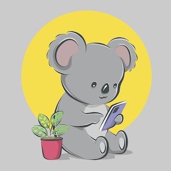 Śliczna koala siedzi i obsługuje smartfon