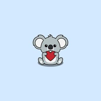 Śliczna koala trzyma czerwony kreskówka w kształcie serca