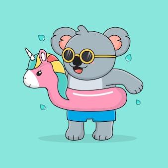Śliczna koala z jednorożcem w pierścieniu do pływania i okularami przeciwsłonecznymi