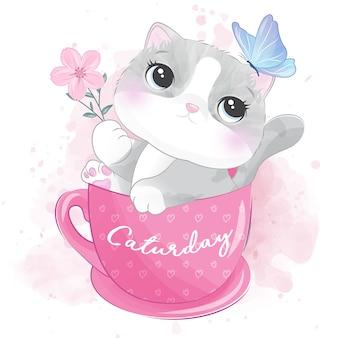 Śliczna kotka w filiżance bawi się motylem