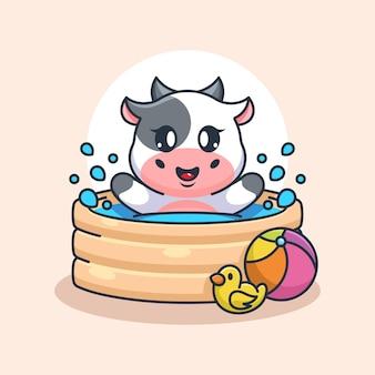 Śliczna krowa bawiąca się w nadmuchiwanym basenie