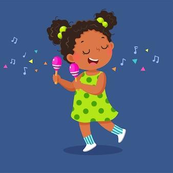 Śliczna mała dziewczynka gra na marakasach