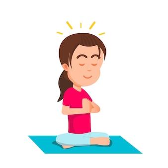 Śliczna mała dziewczynka medytuje w spokojnym nastroju